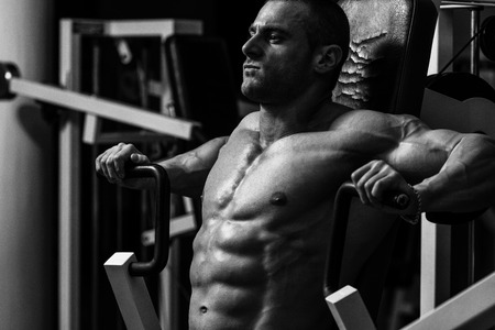 bodybuilding: Male Bodybuilder Doing Heavy Weight Exercise For Chest Stock Photo