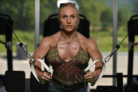 crossover: Woman Bodybuilder Is Working On Her Chest With Cable Crossover In Gym