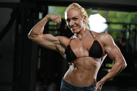 mujer deportista: Mujer seria Bodybuilder Permanente en el gimnasio y Flexionar los m�sculos