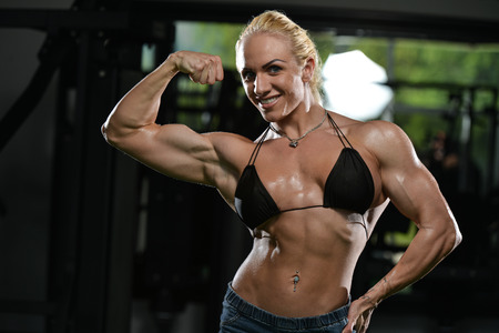female athlete: Serious Woman Bodybuilder Standing In The Gym And Flexing Muscles