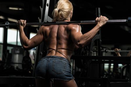 Female Bodybuilder Doing Heavy Weight Exercise For Legs Barbell Squat photo