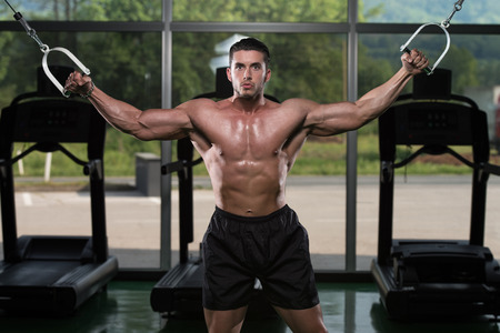 crossover: Bodybuilder Is Working On His Chest With Cable Crossover In Gym Stock Photo