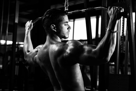 Young Bodybuilder Doing Heavy Weight Exercise For Back In Gym Stock Photo