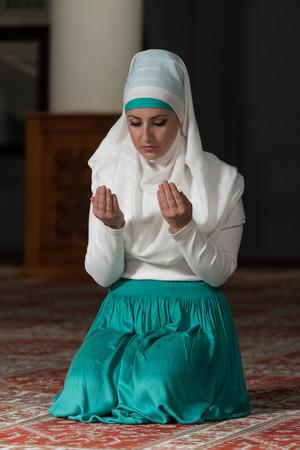 Young Muslim Woman Praying In Mosque photo