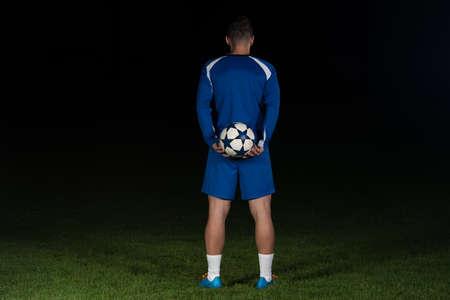 Rückseitige Ansicht der Fußballspieler in der blauen Uniform auf schwarzem Hintergrund isoliert Standard-Bild