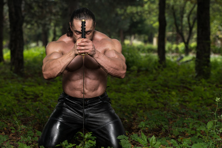 Action Hero Muscled Man Holding A Ancient Sword - Standing In\ Forest Wearing Leather Pants