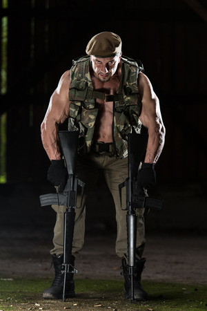 Action Hero Muscled Man Holding Machine Guns - Standing In\ Abandoned Building Wearing Green Pants