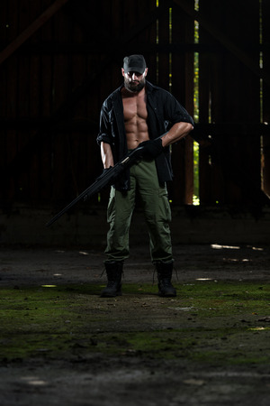 Action Hero Muscled Man Holding Machine Gun - Standing In\ Abandoned Building Wearing Green Pants