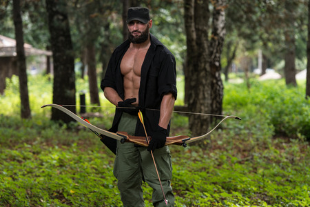 Beard Man With A Bow And Arrows In The Woods Stock Photo