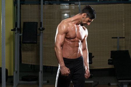 physically fit: Portrait Of A Physically Fit Young Man - Flexing Muscles