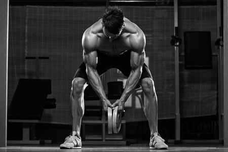 low back: Male Fitness Athlete Doing Heavy Weight Exercise For Back Stock Photo