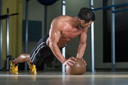 Attraktive Male Athlete Darstellende Liegestütze auf Medizinball