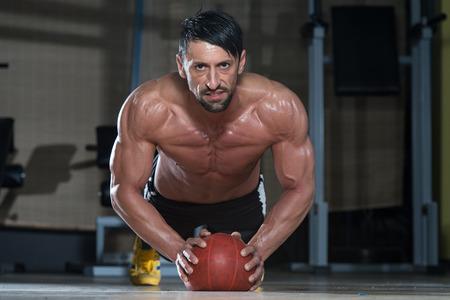 attractive male: Atractivo Atleta Masculino Performing pectorales en bola de medicina