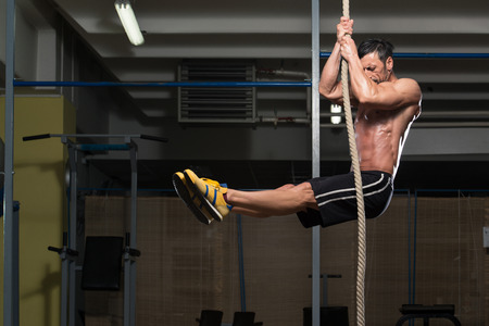 fitness rope climb exercise in fitness gym workout stock photo