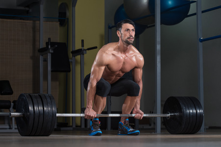 Male Fitness Athlete Lifting Deadlift In The Gym photo