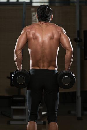 trapezius: Montar Atleta Haciendo Trapecio - flexiones de concentraci�n con mancuernas Foto de archivo