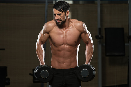 trapezius: Fit Athlete Working Out Trapezius - Dumbbell Concentration Curls Stock Photo