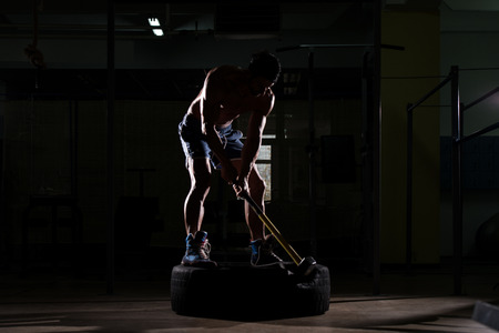 siluet: Athletic Man Hits Tire - Workout At Gym With Hammer And Tractor Tire Siluet Stock Photo