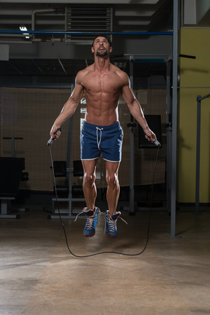Young Man In Gym Is Jumping Rope
