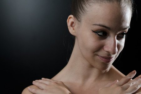Close Up Of A Beautiful Female Ballet Dancer On A Black Background photo