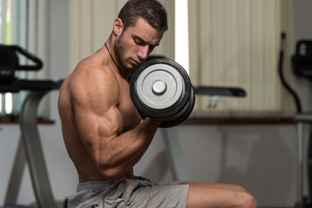 well build: Fit Athlete Working Out Biceps - Dumbbell Concentration Curls Stock Photo