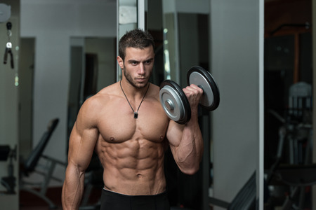 Fit Athlete Working Out Biceps - Dumbbell Concentration Curls Standard-Bild