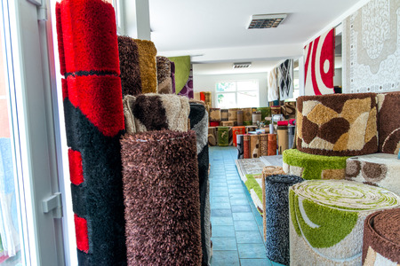 carpet clean: Colorful Collection Of Carpets And Rugs Folded And Displayed. Textured Carpet Surface Detail Specific View