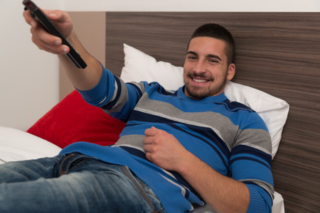 beau jeune homme: Beau jeune homme en regardant la t�l�vision Allong� sur le lit avec la t�l�commande � la main