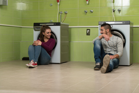 everyday jobs: Pretty Smiling Couples In The Laundry Room Stock Photo