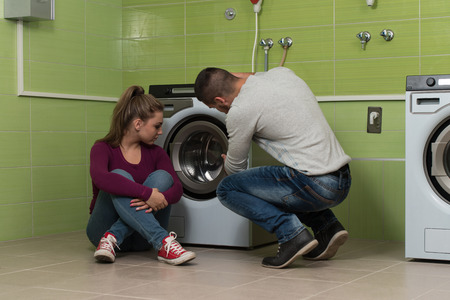 laundry room: Pretty Smiling Couples In The Laundry Room Stock Photo