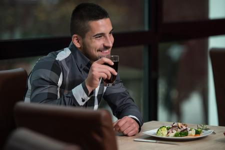 Handsome Man Essen in einem Restaurant und suchen glücklich