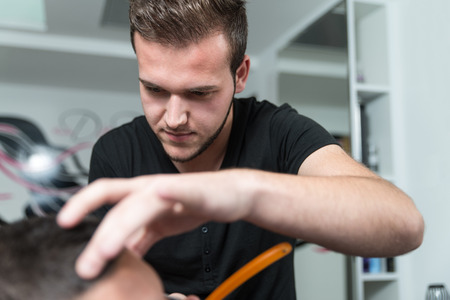 parlor: Handsome Young Hairdresser Giving A New Haircut To Male Customer At Parlor Stock Photo