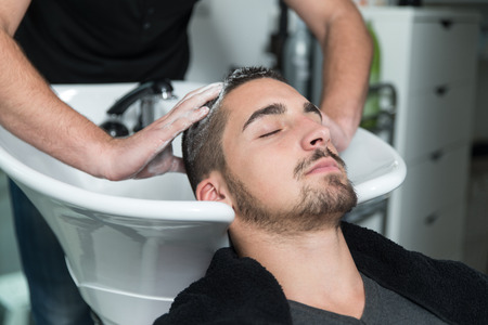 hair cut: Hairstylist Hairdresser Washing Customer Hair - Young Man Relaxing In Hairdressing Beauty Salon Stock Photo