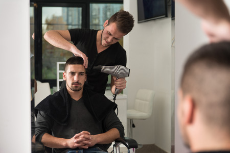haircut: Handsome Man At The Hairdresser Blow Drying His Hair