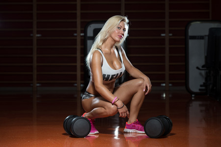 only one girl: Sexy Sporty Woman In The Gym With Exercise Equipment Stock Photo