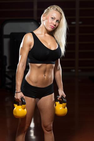 abdomen fitness: Fitness mujer que trabaja con Caldera Campana Foto de archivo