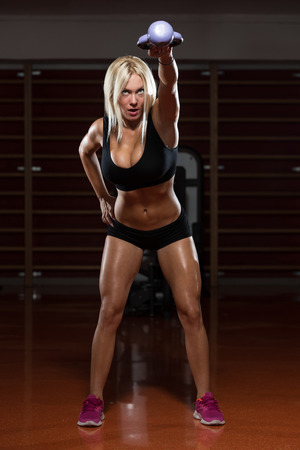 only the biceps: Fitness Woman Working Out With Kettle Bell