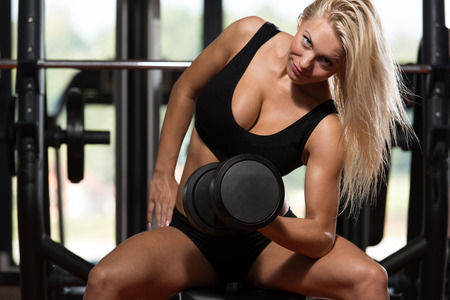 only the biceps: Young Woman Working Out Biceps - Dumbbell Concentration Curls