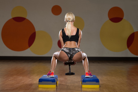body building: Young Woman Performing Dumbbell Barbell Squats - One Of The Best Body Building Exercise For Legs Stock Photo