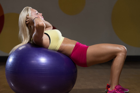 Young Woman Exercising Abdominals In Fitness Club photo