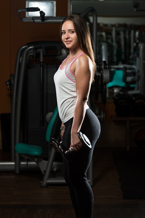 only the biceps: Young Woman Doing Heavy Weight Exercise For Biceps With Dumbbells
