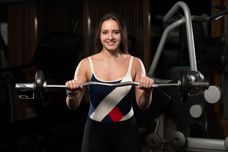 only the biceps: Young Woman Doing Heavy Weight Exercise For Biceps Stock Photo