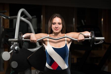 trapezius: Mujer joven que hace Heavy Weight Ejercicio Para Trapecio Foto de archivo