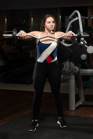 trapezius: Young Woman Doing Heavy Weight Exercise For Trapezius
