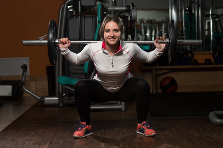 body building: Young Woman Performing Barbell Squats - One Of The Best Body Building Exercise For Legs