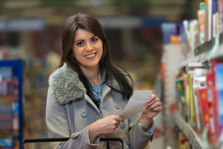 produce departments: Beautiful Young Woman Reading Her Shopping List In Produce Department Of A Grocery Store - Supermarket - Shallow Deep Of Field Stock Photo