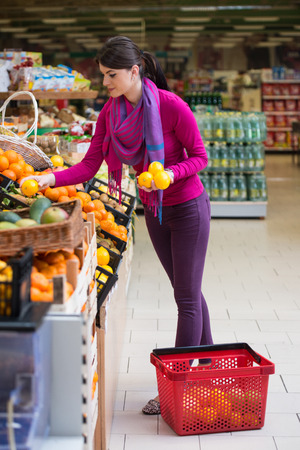produce departments: Beautiful Young Woman Shopping For Fruits And Vegetables In Produce Department Of A Grocery Store - Supermarket - Shallow Deep Of Field Stock Photo