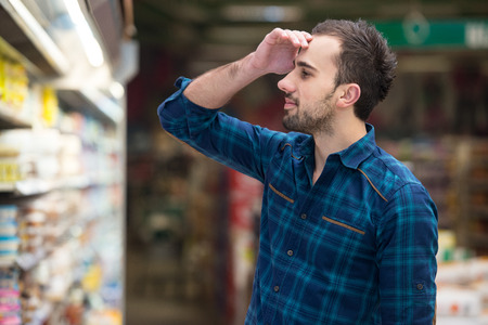 produce departments: Handsome Young Man Shopping For Fruits And Vegetables In Produce Department Of A Grocery Store - Supermarket - Shallow Deep Of Field