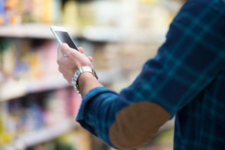 Lächelnder junger Mann mit Handy während Warenkorb Im Einkaufs Shop Standard-Bild