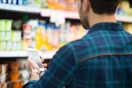 Lächelnder junger Mann mit Handy während Warenkorb Im Einkaufs Shop Lizenzfreie Bilder